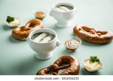 Deutsche Münchener Weißwurst in Porzellantopf, bayerischer SüßSenf, Butter und Brezel auf pastellgrünem Hintergrund