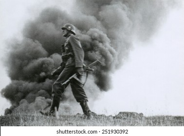 German officer of assault troops during the Nazi invasion of the Soviet Union, (Russia) In the Summer of 1941, the soldier strides against a background of burning buildings, during World War 2.