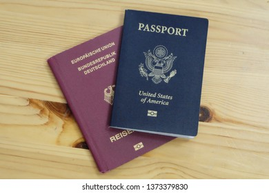 German passport, and American passport with wood background.