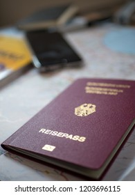 German passport with map, smartphone and travel accessories in background