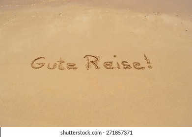 The German phrase 'Gute Reise' (translated: Have a good trip) written in the sand at the beach