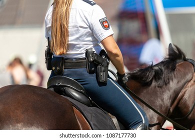 German police horsewoman rides on a police horse. The german word Polizei means police.