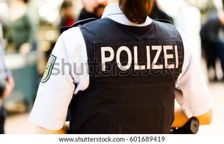 German police officer woman on the Hamburg airport observes passengers. Back shot focus on bulletproof vest with Polizei badged. Flughafen Hamburg, 13 March 2017