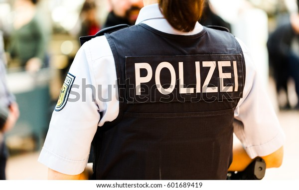 German police officer woman on the Hamburg airport observes passengers. Back shot focus on bulletproof vest with Polizei badged. Flughafen Hamburg, 13 March 2017