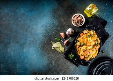 German, polish, Austrian cuisine dish, Bigos - sauerkraut cabbage stewed with meat, mushrooms and sausages, in small pan on dark concrete background.Top view with copy space.