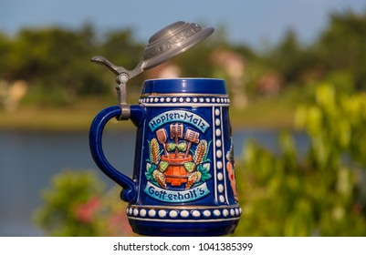 """A German porcelain beer stein with a hinged pewter lid and there is a toast on it: """"Hopfen + Malz, Gott erhalt's""""."""