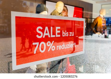 German sale sign with the writing up to 70 percent reduced hanging at the shop window of an apparel store