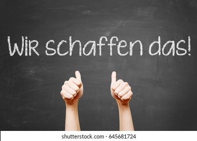 "German slogan ""Wir schaffen das"" (we can do it) with thumbs up on blackboard"