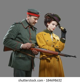 A German soldier with the lady on the hunt. Isolated on gray.
