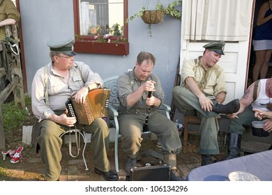German soldiers relaxing during World War II reenactment with musical instruments at French Village at Mid-Atlantic Air Museum World War II Weekend and Reenactment in Reading, PA held June 18, 2008