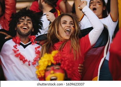 German spectators in stadium cheering their national team. People from Germany in fan zone jumping and chanting for their soccer team.