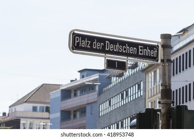 German street signs with blue sky and building in background