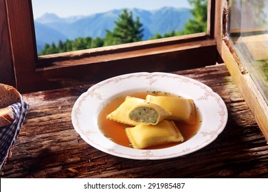 German Stuffed ravioli pasta squares in a savory sauce cut through to reveal the vegetable stuffing and served on a rustic wooden windowsill overlooking the Bavarian alps