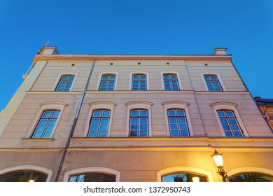 German style residential building. Illuminated facade in the early morning.