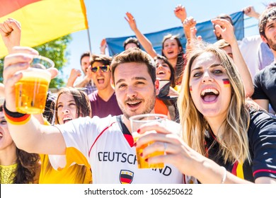German supporters celebrating at stadium and drinking beer. Group of fans watching a match and cheering team Germany. Sport and lifestyle concepts.