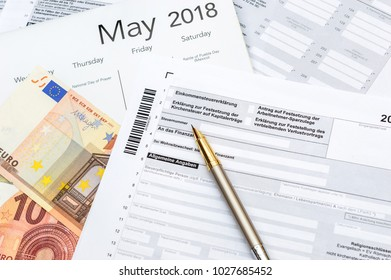 German tax form with money and calendar. Translation:(Income tax declaration, declaration of church tax , employee savings allowance, number, tax office, change of domicile, general information)