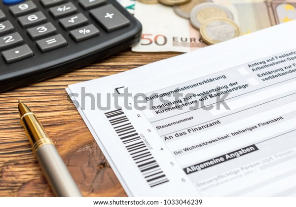 German tax form with pen,money and calculator on the table. Close up. Translation:(Income tax declaration,  church , tax number, tax office, change of domicile, general information)