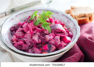 German traditional salad with beets, apple, egg and herring in a bowl, selective focus