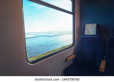 German train interior with an empty blue chair at the window with the Wadden sea view, traveling on the Hindenburg Damm to reach the Sylt island.
