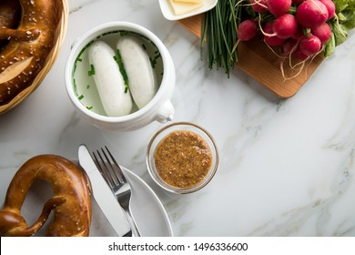 German Weißwurst white sausage in porcelain pot, Bavarian sweet mustard, butter, chives, radish and pretzel on marble table
