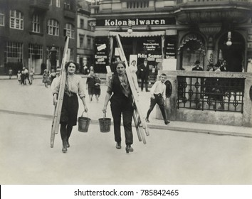 German women window cleaners dressed for work carry their tools in a Berlin street in World War 1. 1914-1918