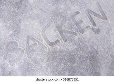 the german word backen on flour background