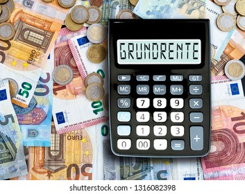 German word GRUNDRENTE (basic pension) written on display of pocket calculator against cash money on table