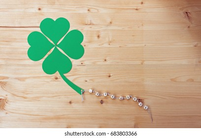 The german words for Good Luck and a cloverleaf on a cord on wood