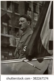 GERMANY -  1937: German leader Adolf Hitler stands in his convertible. Reproduction of antique photo.