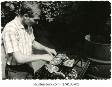 GERMANY -  1950s: An antique photo shows man grilling sausages on the grill