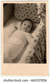 GERMANY - 1954: Vintage photo shows cute small baby in a cot (crib, baby bed). Retro black & white photography.