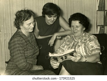 GERMANY - 1960s: An antique photo shows three women of different generations look fashion magazine
