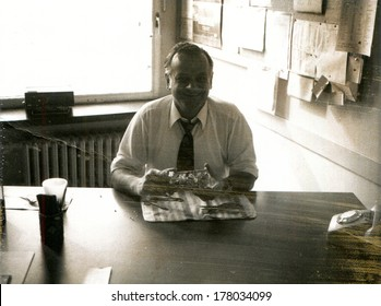 GERMANY -  1960s: An antique photo shows man in white shirt and tie sitting at a table with his back to the window