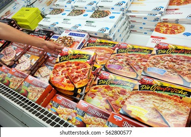 GERMANY - AUGUST 11,  2015: Freezer contains frozen pizza for home cooking in a REAL hypermarket in Germany. Mass-produced pizzas have been criticized as having an unhealthy balance of ingredients.