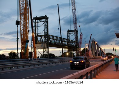 Huntebrück, Germany - August 24, 2018: historic Hunte bridge with cranes for deconstruction seen at dawn from the new bridge across the river Hunte