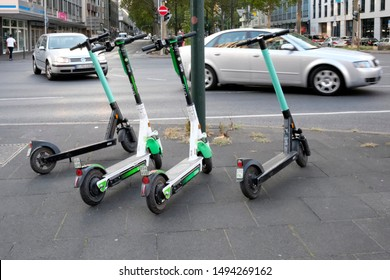 Düsseldorf, Germany - August 30, 2019: E-mobility in Germany: E-scooters waiting for customers next to a pedestrian road in Düsseldorf, Germany, as cars go by.