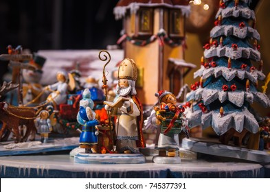 GERMANY, BAMBERG - JANUARY 2, 2017: German wooden handmade toys in the window of the festive store. St. Nicholas hand out gifts to children around Christmas tree.