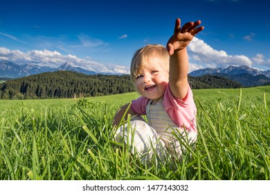 Germany, Bavaria, Allgaeu, happy baby girl playing in the fields
