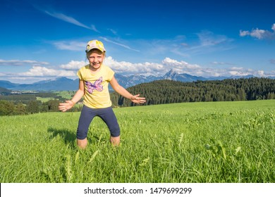 Germany, Bavaria, Allgaeu, happy girl cheering in the fields