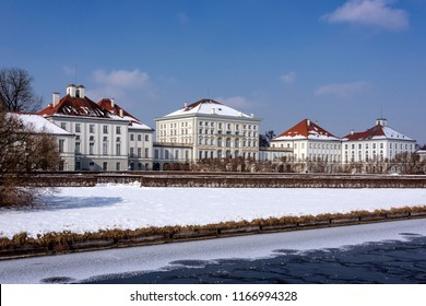 Germany, Bavaria, Munich, Nymphenburg Palace: Panorama view of winter scene with main building entrance of the famous castle, snow, ice, canal, blue sky in the Bavarian capital - concept history