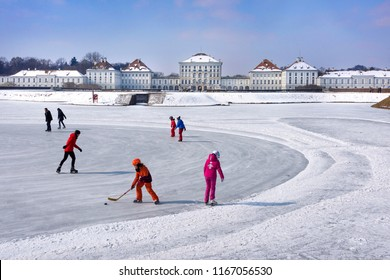 Germany, Bavaria, Munich, Nymphenburg Palace: Happy colorful dressed people men women children while ice skating on white frozen lake water at winter time - concept winter activity. February 28, 2018