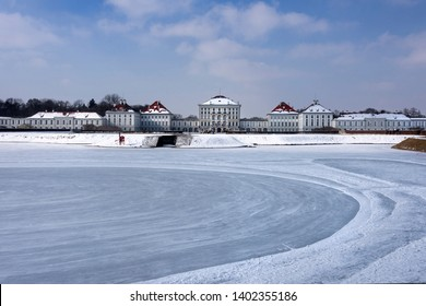 Germany, Bavaria, Munich, Nymphenburg Palace: Panorama view of winter scene with frozen pond lake and main building entrance of the famous castle, white snow, blue sky in the snowy Bavarian capital.
