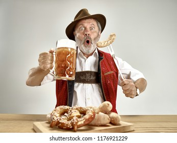 Germany, Bavaria, Upper Bavaria. The senior happy smiling man with beer dressed in traditional Austrian or Bavarian costume holding mug of beer at pub or studio. The celebration, oktoberfest, festival