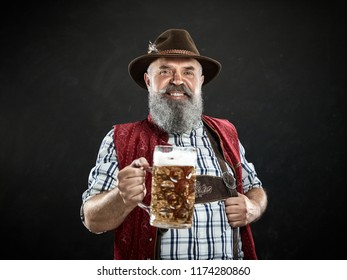 Germany, Bavaria, Upper Bavaria. The smiling man with beer dressed in in traditional Austrian or Bavarian costume in hat holding mug of beer at studio