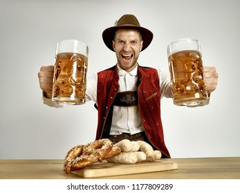 Germany, Bavaria, Upper Bavaria. The young happy smiling man with beer dressed in traditional Austrian or Bavarian costume holding mug of beer at pub or studio. The celebration, oktoberfest, festival