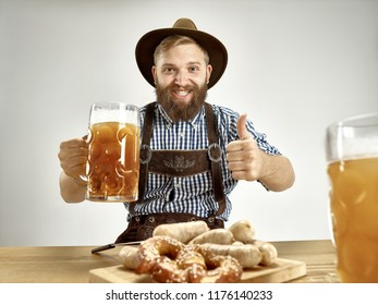 Germany, Bavaria, Upper Bavaria. The young smiling man with beer dressed in traditional Austrian or Bavarian costume in hat holding mug of beer at studio