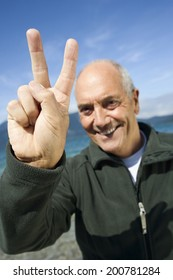 Germany, Bavaria, Walchensee senior man showing victory sign