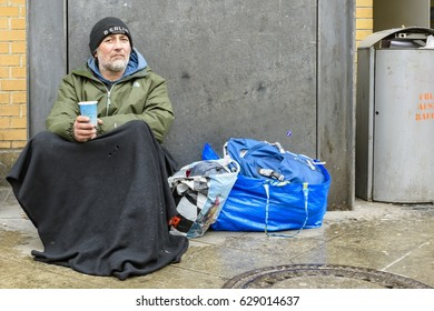 Germany , Berlin , 16.04.2017 , Homeless sits on a wall and begs