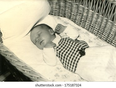 GERMANY, BERLIN -  CIRCA 1950s: An antique photo shows baby sleeping in a wicker wheelchair