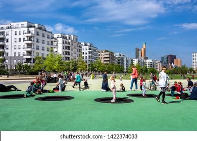 Germany, Berlin, Kreuzberg Schoneberg, Park am Gleisdreieck: People kids men women have fun in the city center of the German capital with famous Potsdamer Platz and blue sky - leisure. May 01, 2019